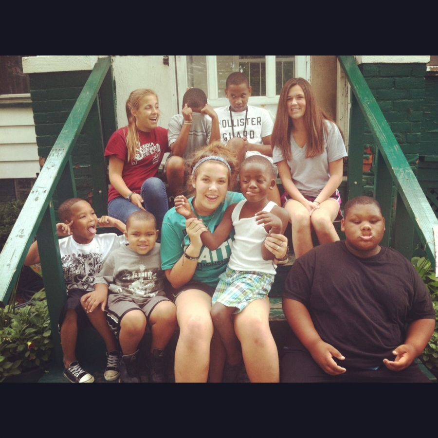 Emily Potter [center, in blue] sits with friends and underprivileged children in Detroit.  PHOTO / EMILY POTTER