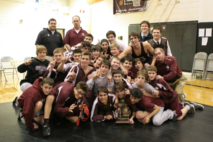 The Seaholm wrestling team poses with the Division 1 District Championship trophy. They defeated Groves in the first round and Brother Rice in the second round to win the title.  PHOTO / KEN TASHIRO