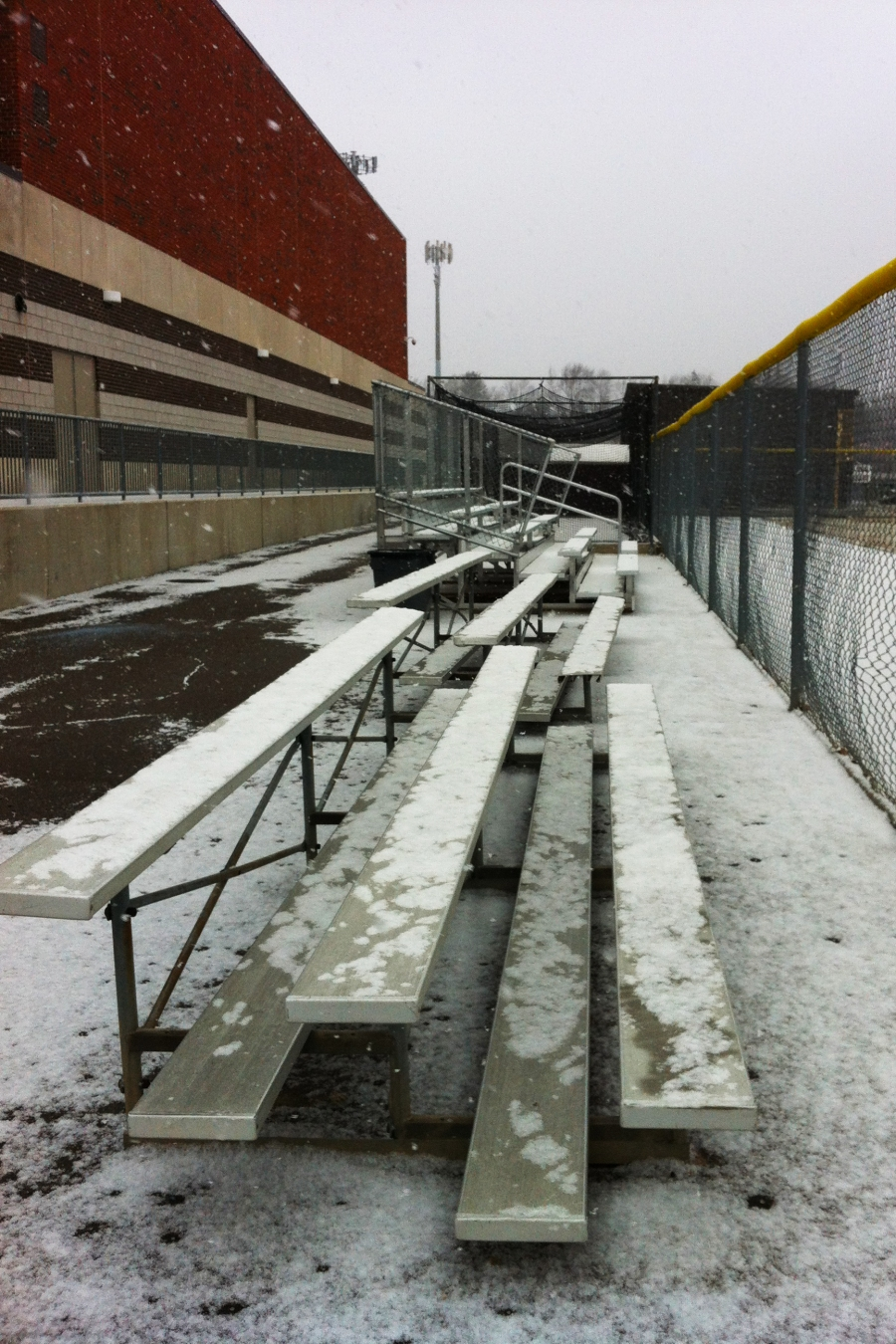 Snow settles on Seaholm's softball bleachers March 19. Cold temperatures have remained in Metro-Detroit since late 2012.  PHOTO / CAROLINE SQUATRITO